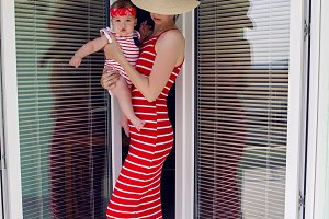 mother with a baby in a red striped dress and a hat stands