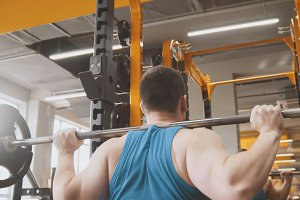 Fitness gym - muscular man performs squats with barbell - rear view