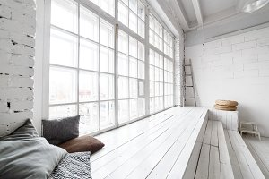 Bright photo studio interior with big window, high ceiling, white wooden floor