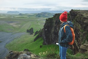 woman hiker with backpack siting on top of a mountain and enjoying sunset in Iceland