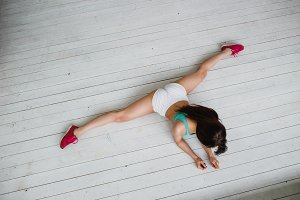 Flexible latina girl doing stretching exercise for legs. Young woman stretches out on white floor. Top view.