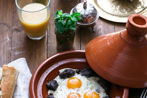Sunnyside Eggs cooked in a Tajine dish with beef, Moroccan breakfast with juice and mint tea