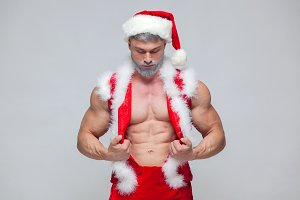 Christmas. Sexy Santa Claus . Young muscular man wearing Santa Claus hat demonstrate his muscles.