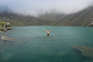 A man is bathing in a cold mountain lake in rainy weather. Lake of mountain spirits, Altai, Russia.