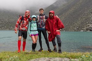 Happy friends relax on lake. People enjoy beautiful lake and good rainning weather in Altai, Russia