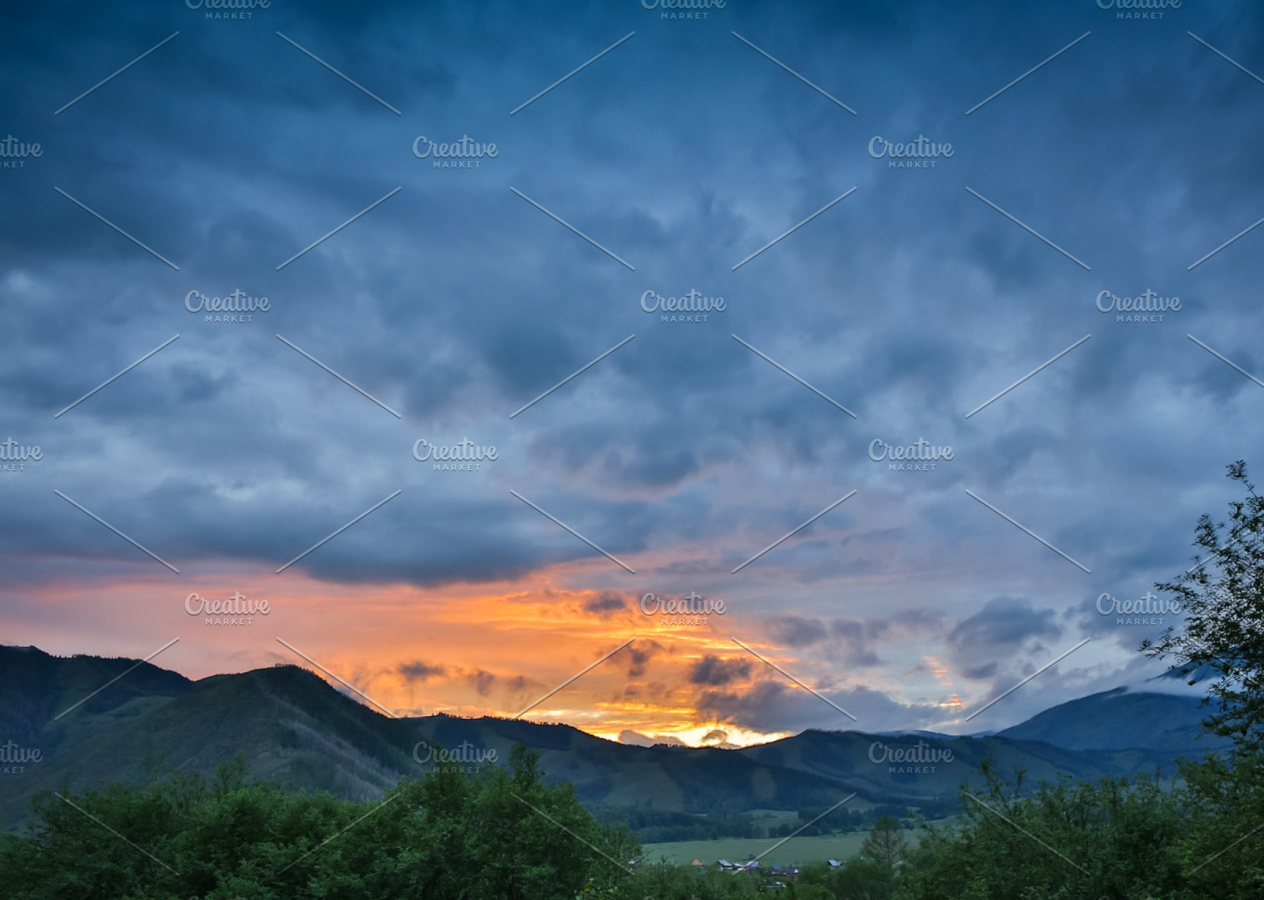 Beautiful Dramatic Sunset In The Mountains Landscape With Sun Light Shining Through Orange Clouds