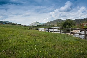 Spring Landscape of Green Meadow with Wooden Fence along River under Blue Sky