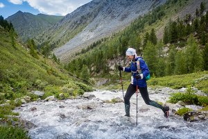 The girl runs along the mountain river, participate in competitions in the mountains of Altai, Russia.