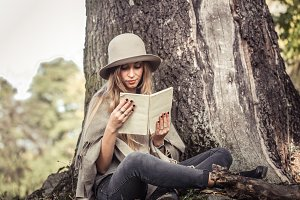 girl in a hat reading a book in autumn forest
