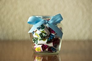 A glass jar with a bow full of candy