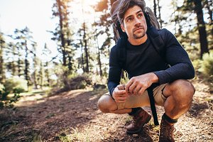 Man sitting on forest trail