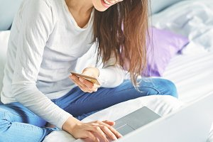 a young smiling woman with laptop and credit card