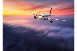 Modern airplane mith motion blur effect is flying over low cloud