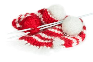 Red woolen scarf and balls of yarn