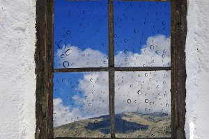 Mountain with clouds and blue sky behind the rain in the old wooden window in the wall