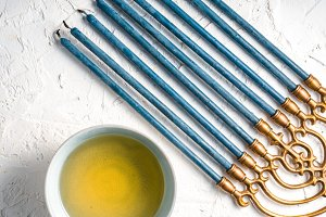 Brass Hanukiya Menorah with blue candles and butter in a bowl diagonal