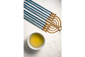 Menorah brass Hanukkah with blue candles and butter in a bowl on a white table