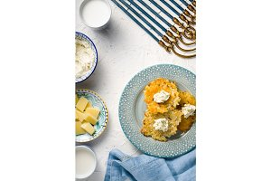 Latkes, cheese, milk and curd cheese, Hanukkah on white table free space