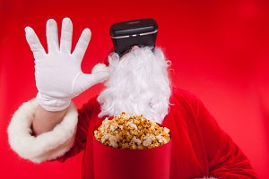 Santa Claus wearing virtual reality goggles and a red bucket with popcorn, on a red background. Christmas