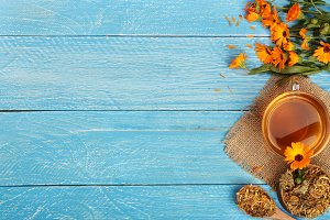 Calendula tea with fresh and dried flowers on blue wooden background with copy space for your text. Top view