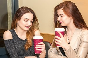 Two young girls talking in a cafeteria