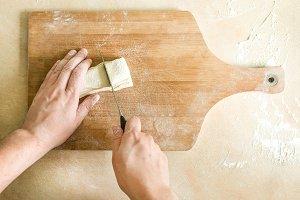 Men's hands cutting raw dough
