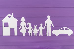 The silhouettes cut out of paper of man and woman with two girls and boy house and car near
