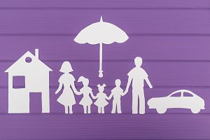 The silhouettes cut out of paper of man and woman with two girls and boy under the umbrella, house and car near