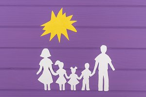 The silhouettes cut out of paper of man and woman with two girls and boy under the sun