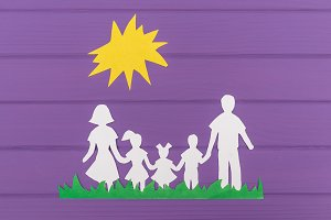 The silhouettes cut out of paper of man and woman with two girls and boy on the grass under the sun