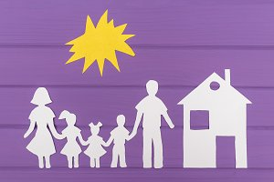 The silhouettes cut out of paper of man and woman with two girls and boy under the sun, house near