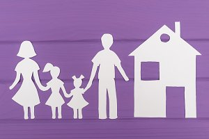 The silhouettes cut out of paper of man and woman with two girls, house near