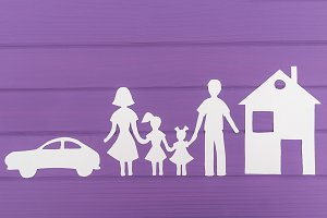 The silhouettes cut out of paper of man and woman with two girls, house and car near