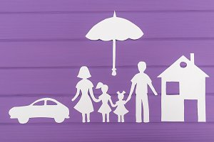 The silhouettes cut out of paper of man and woman with two girls under the umbrella, house and car near