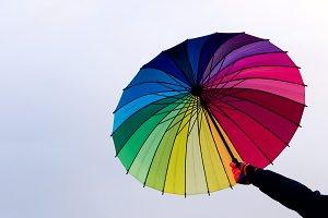Umbrella in hand against sky background
