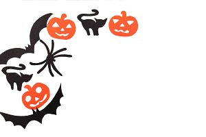 Silhouettes of black volatile bats, cats, orange pumpkins, cats and spider carved out of black paper are isolated on white