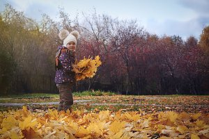 Happy Little child baby girl playing in Autumn