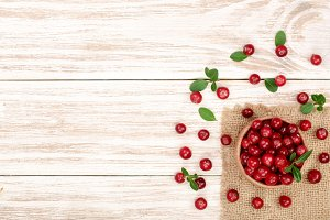 Cranberry with leaf in bowl on white wooden background with copy space for your text. Top view