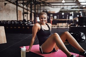 Fit young woman sitting on a gym floor smiling