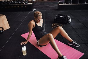 Fit young woman sitting on the floor of a gym