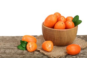 Cumquat or kumquat with leaf in wooden bowl on old wooden table with white background