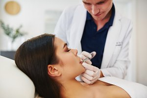 Focused doctor doing botox injections on a young woman's lips