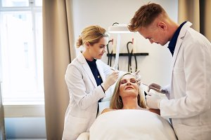 Doctor and assistant performing botox injections on a mature woman