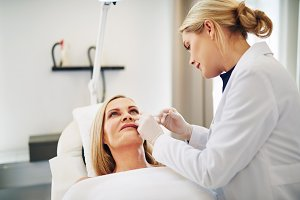 Doctor injecting botox into the cheek of a mature woman
