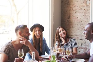 Laughing friends having wine and a meal together
