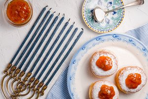 Donuts with apricot jam on a ceramic plate and Hanukkah top view