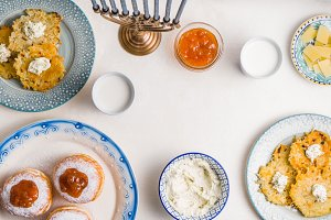 Plates with latkes, donuts, curd cheese for a festive feast