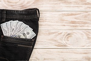 american dollar bills in jeans pocket on white wooden background with copy space for your text. Top view