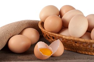 eggs on a wooden table in a wicker basket on a white background