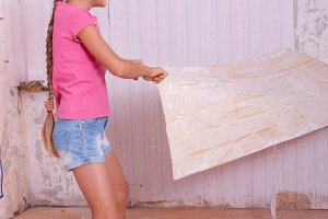 girl remove old wallpapers from wall